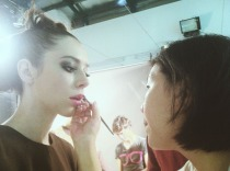 Make up artist touch up on model